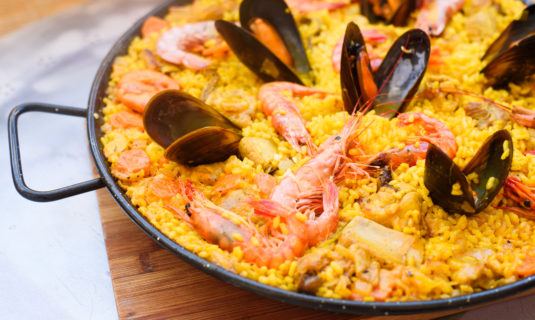 Closeup of a traditional tasty spanish dish paella served with prawns and mussels